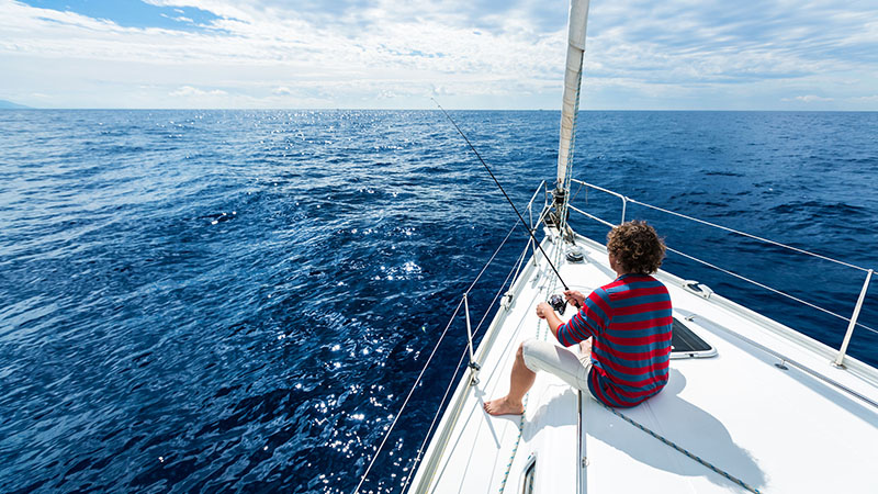 53541510 - man fishing in a calm sea from a sail boat